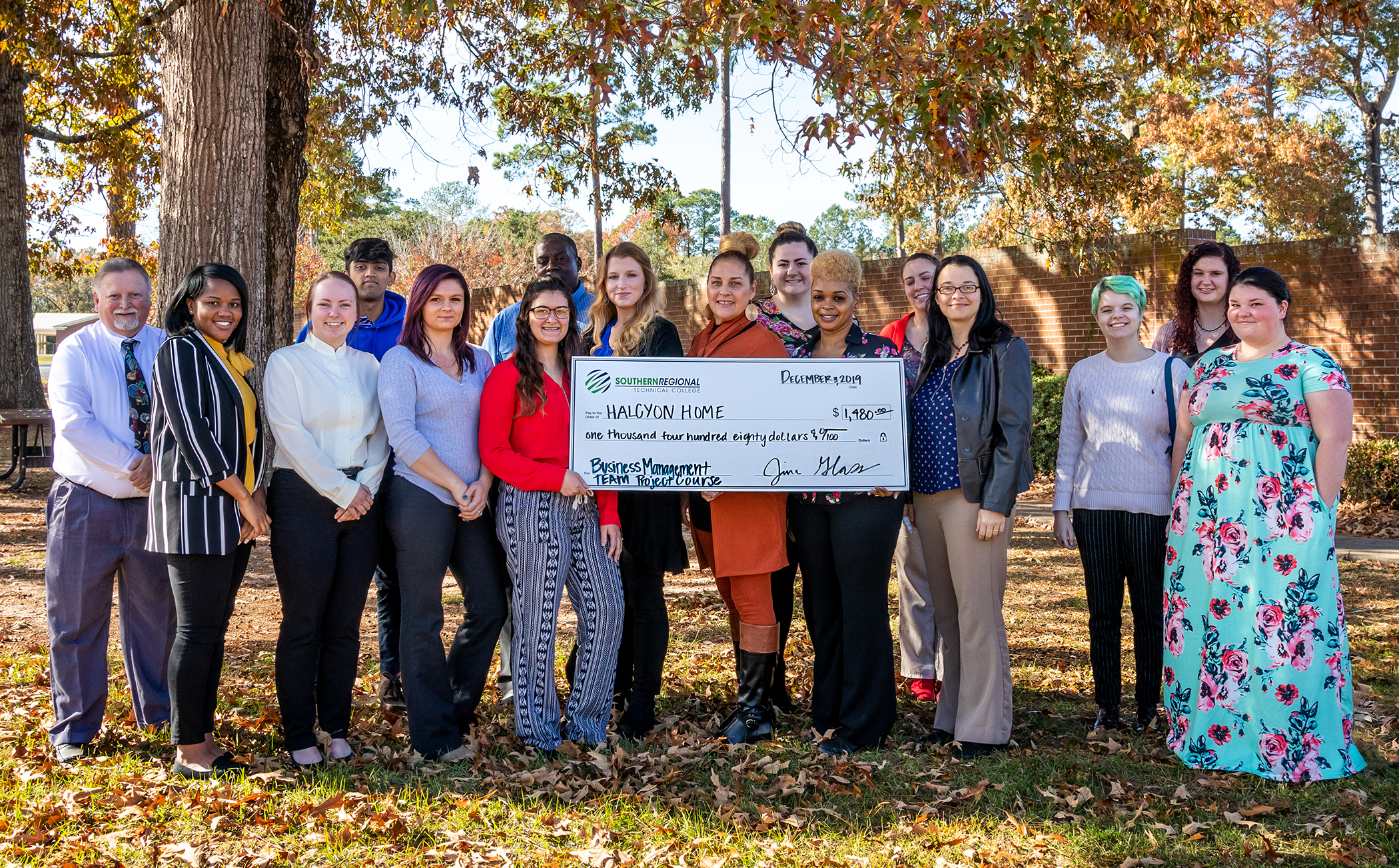 Students hold large check for donation presentation.