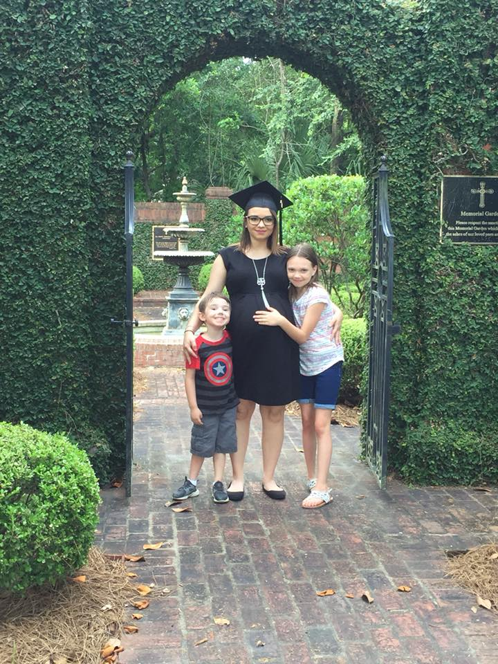 Graduate Marlana Bays in the garden of All Saints Church with her son and her daughter.